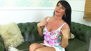 Cute brunette mom slowly gets naked on the sofa